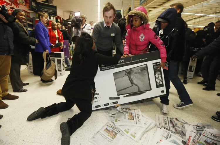"Shoppers wrestle over a television as they compete to purchase retail items on ""Black Friday"" at an Asda superstore in Wembley, north London November 28, 2014. Britain's high streets, malls and online sites were awash with discounts on Friday as more retailers than ever embraced U.S.-style ""Black Friday"" promotions, seeking to kickstart trading in the key Christmas period. In the United States the Friday following the Thanksgiving Day holiday is called Black Friday because spending usually surges and indicates the point at which American retailers begin to turn a profit for the year, or go ""into the black"". REUTERS/Luke MacGregor (BRITAIN - Tags: BUSINESS ANNIVERSARY TPX IMAGES OF THE DAY)"